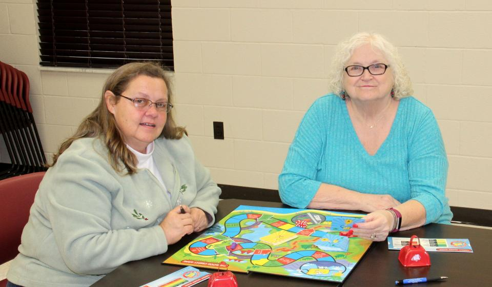 Two Todd County Ladies setting at a table playing a board game